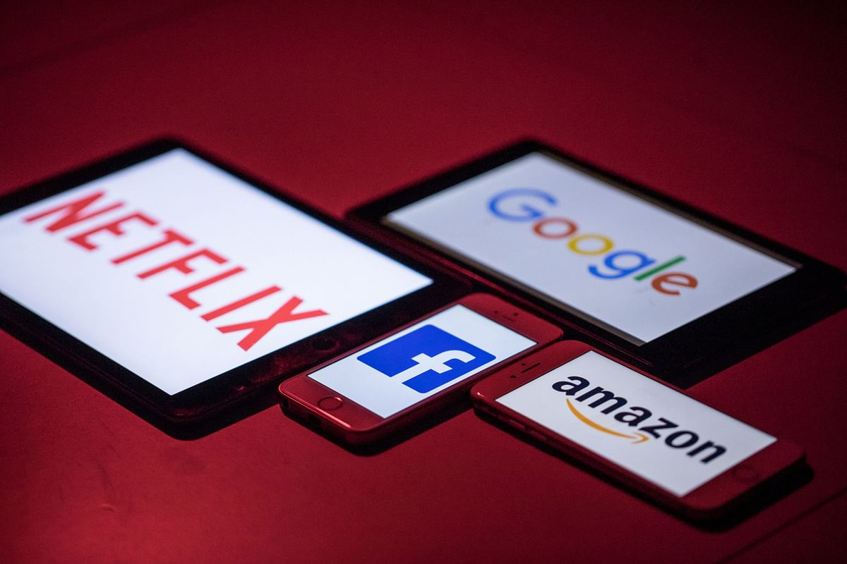 The logos for Facebook, Amazon, Netflix, and Google on smartphone and tablet devices. (Photographer: Jason Alden/Bloomberg)