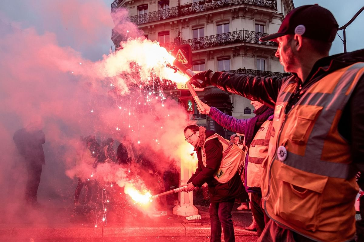 Protesters wave burning flares during a day of unrest over French pension reform plans in Paris on Jan. 9. Photographer: Anita Pouchard Serra/Bloomberg