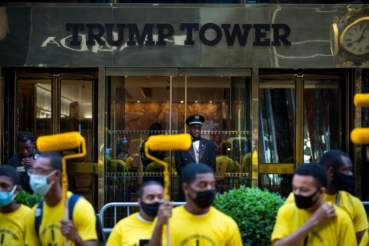 A doorman at Trump Tower watches volunteers paint a Black Lives Matter mural along Fifth Avenue in New York on July 9. Trump sent heavily armed agents to U.S. cities where they often beat, gassed and shot at protesters. Photographer: Michael Nagle/Bloomberg