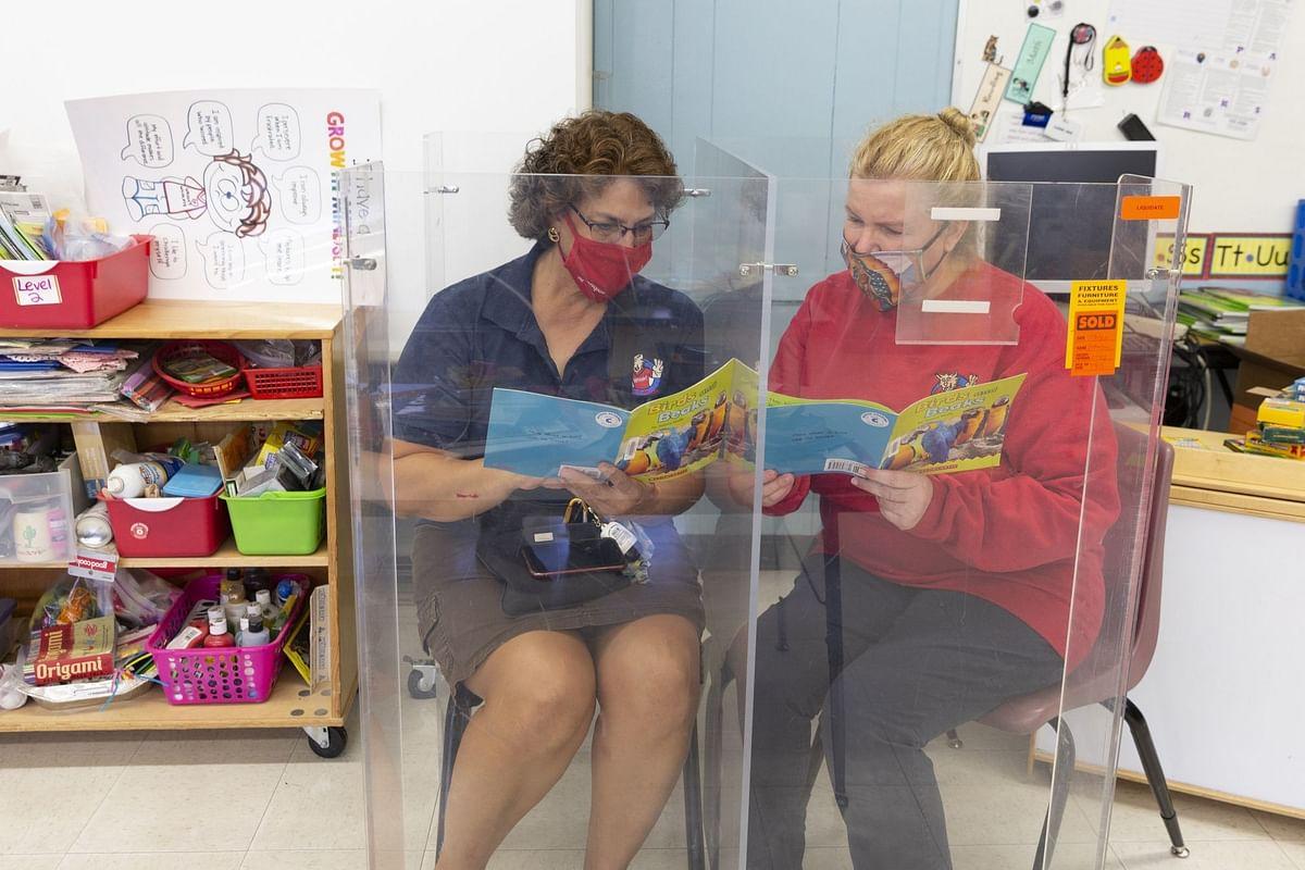 Teachers demonstrate a plexiglass reading corner at an elementary school in Tucson, Arizona, on Aug. 14. Photographer: Cheney Orr/Bloomberg
