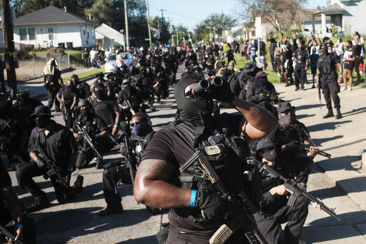 Armed anti-police violence demonstrators keep watch during a protest in Kentucky on Sept. 5. They gathered after Breonna Taylor, a Black emergency medical technician, was shot dead by White Louisville police as she slept in her home. Photographer: Matthew Hatcher/Bloomberg
