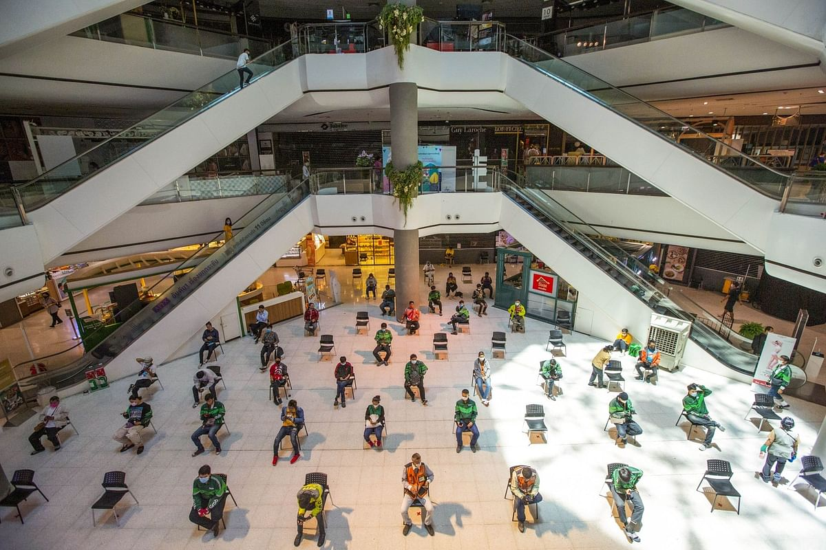 Food delivery couriers wait in a mall in Bangkok on March 30. As Covid-19 lockdowns fell into place all over the world, home delivery of goods and services skyrocketed. Photographer: Andre Malerba/Bloomberg