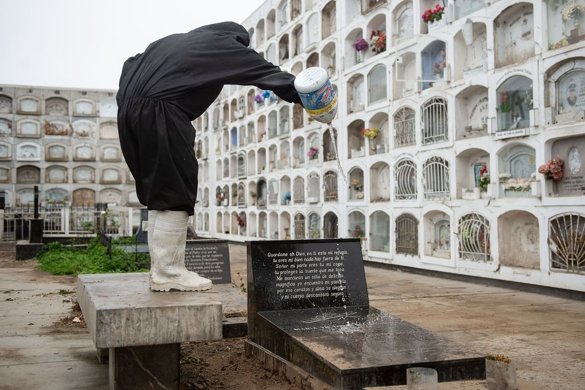 A worker pours bleach on the grave of a Covid-19 victim at the El Angel cemetery in Lima, Peru, on June 3. Photographer: Miguel Yovera/Bloomberg