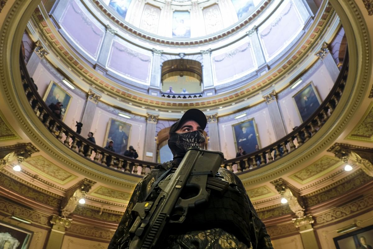An armed protester at the Michigan Capitol Building in Lansing on April 30. Far-right groups demonstrated against Covid-19 lockdowns throughout the year. Photographer: Matthew Hatcher/Bloomberg