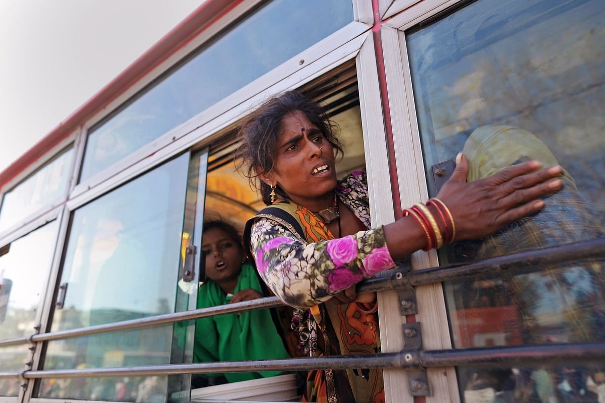 A migrant worker shouts to her child from a bus on the outskirts of New Delhi on March 29, during India's lockdown. Millions of laborers were forced to return to their hometowns and villages as jobs in the cities vanished. Photographer: Anindito Mukherjee/Bloomberg