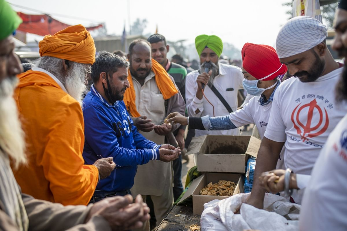 Farmers distribute food at a protest site at a road block on the Delhi-Haryana border crossing in Singhu, Delhi, India. (Photographer: Prashanth Vishwanathan/Bloomberg)