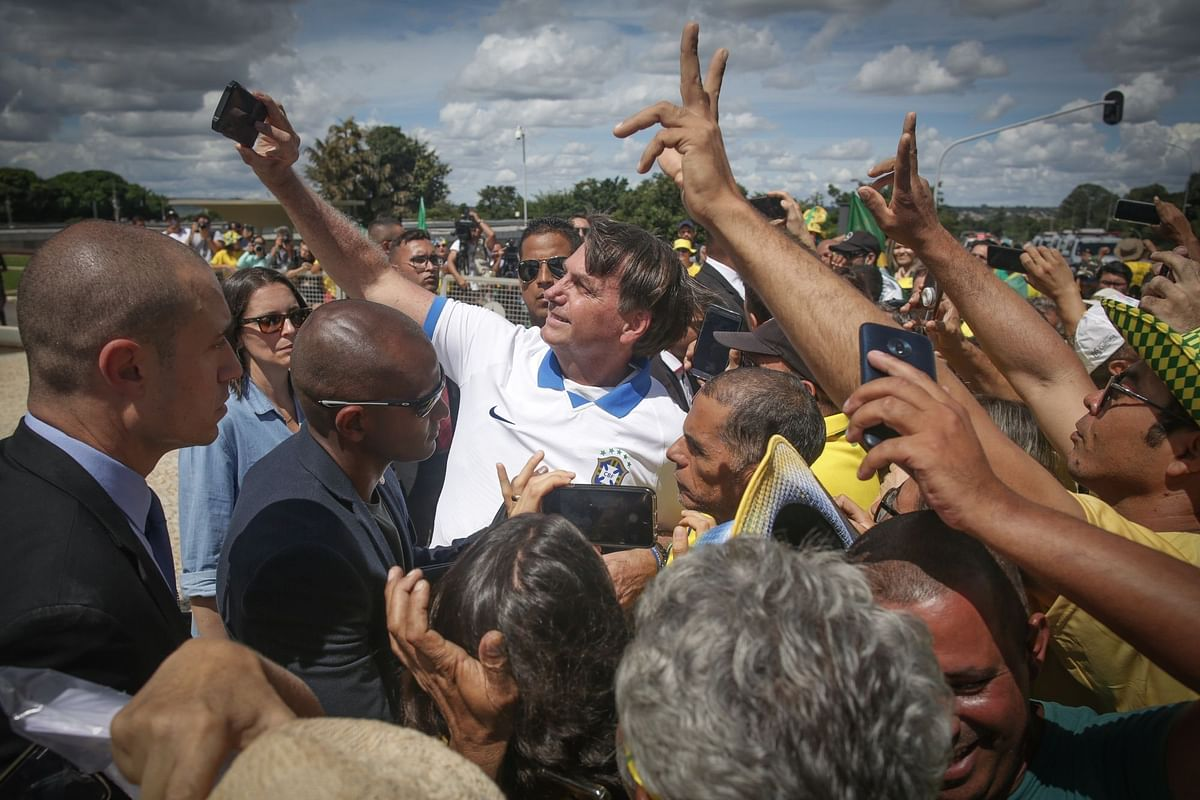 Brazil President Jair Bolsonaro, who later became infected with Covid-19, takes a selfie with supporters during a demonstration in Brasilia on March 15. Photographer: Andre Coelho/Bloomberg