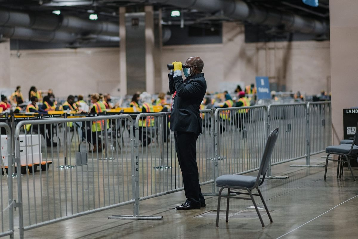 In Philadelphia, a poll watcher uses binoculars to monitor the count in the U.S. presidential election that took place on Nov. 3. Photographer: Hannah Yoon/Bloomberg