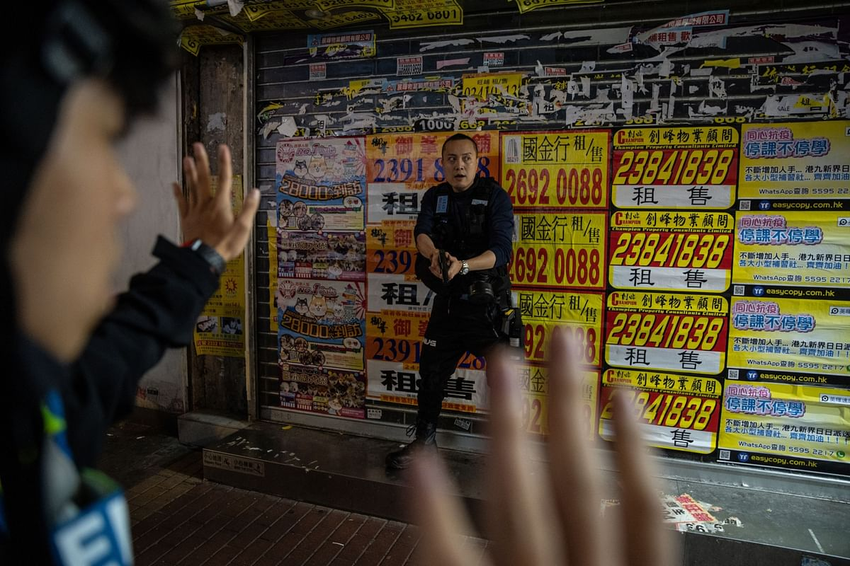 A police officer draws his weapon during democracy protests in the Mong Kok district of Hong Kong on Feb. 29. Photographer: Roy Liu/Bloomberg