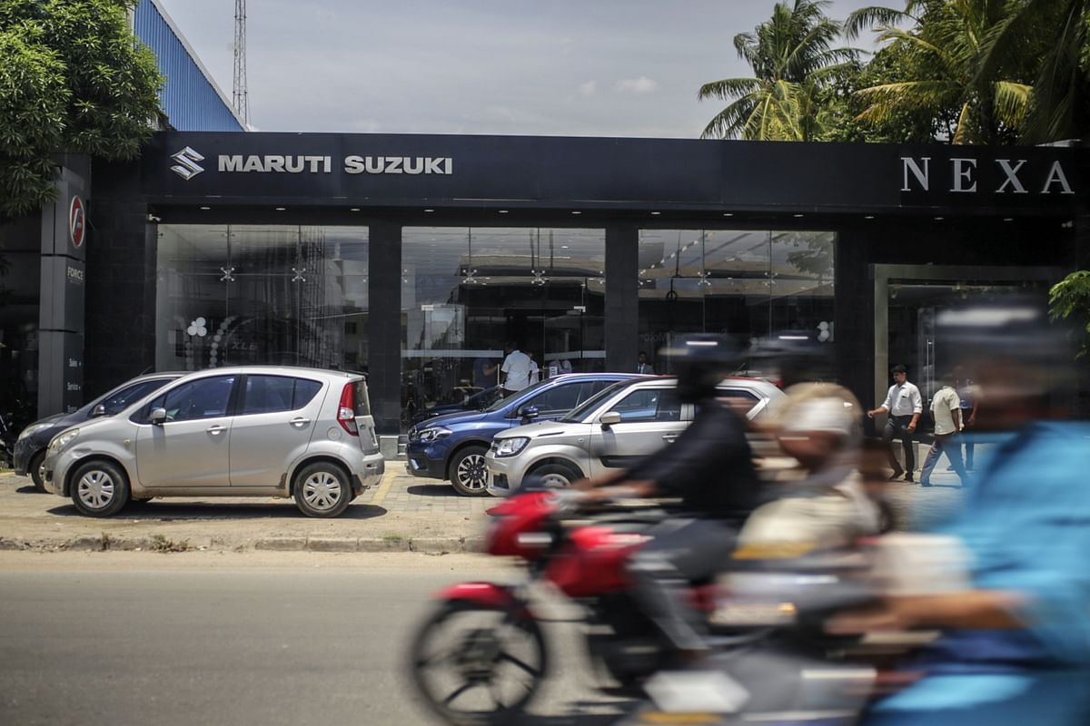 Motorcyclists ride past a Maruti Suzuki India Ltd. showroom in Chennai. (Photographer: Dhiraj Singh/Bloomberg)