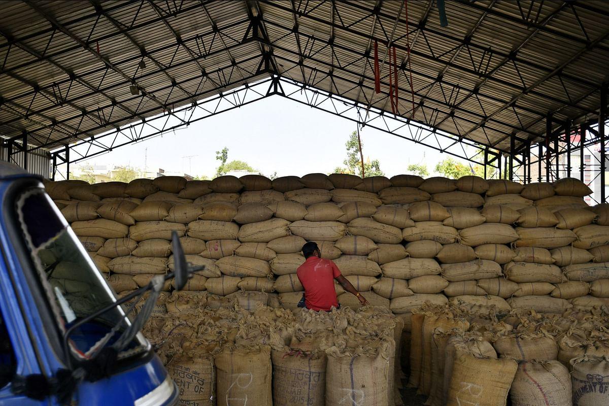 A man sits on sacks of grain at a wholesale grain market in Rewari, Haryana, India, on March 28, 2018. (Photographer: Anindito Mukherjee/Bloomberg)