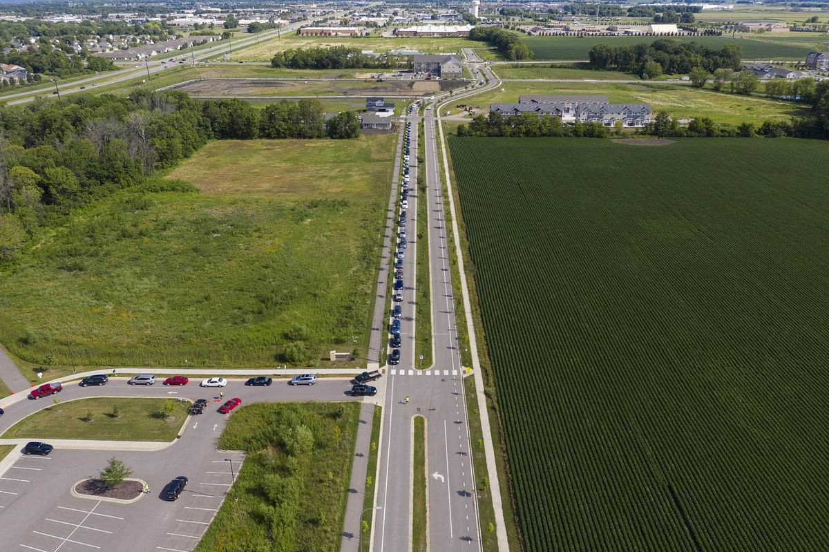 Drivers line up alongside fields of crops at a charity food pantry in Mankato, Minnesota, on July 23.  Photographer: Ben Brewer/Bloomberg