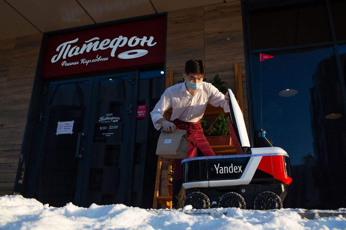 A restaurant worker places an order in an autonomous delivery robot in Innopolis, Russia, on Dec. 1. Photographer: Andrey Rudakov/Bloomberg
