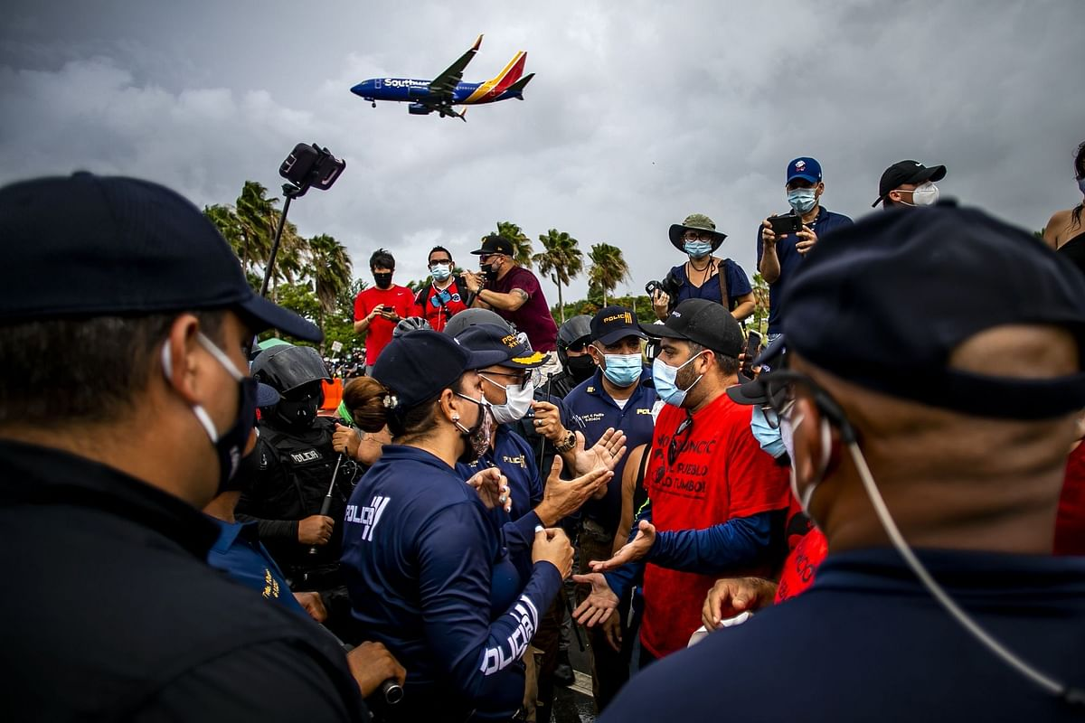 Police officers confront demonstrators in Puerto Rico during a protest against U.S. mainland tourists arriving from coronavirus hot zones on July 25. Photographer: Xavier Garcia/Bloomberg