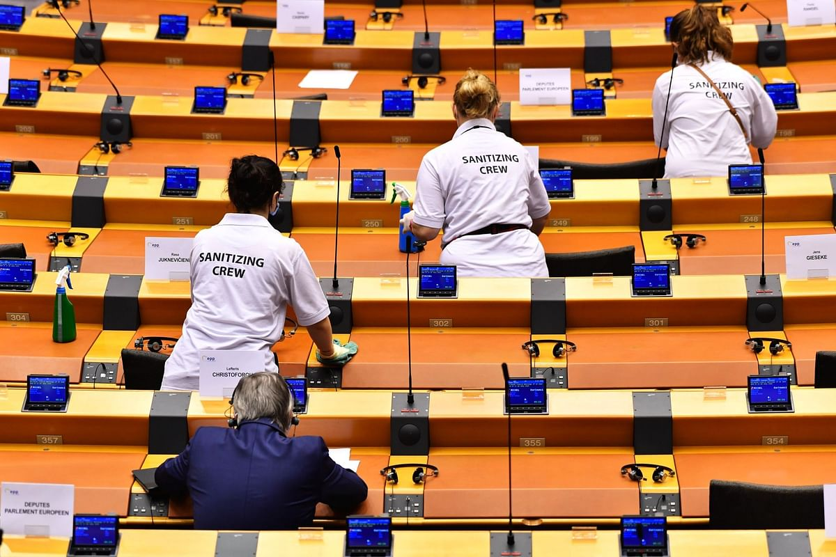 A sanitizing crew cleans desks at the European Parliament in Brussels on July 8. Photographer: Geert Vanden Wijngaert/Bloomberg