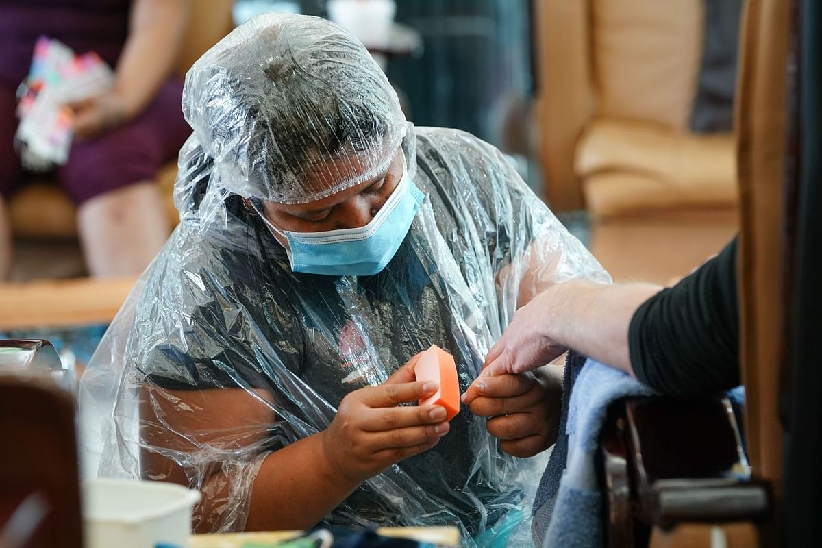 A nail salon worker giving a manicure in Atlanta on April 24. Personal care services have been especially hard hit by the pandemic. Photographer: Elijah Nouvelage/Bloomberg