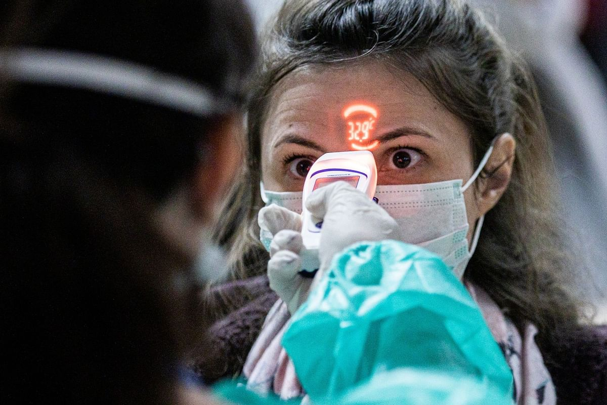A passenger arriving from Italy in Debrecen, Hungary, gets a temperature check on Feb. 24. Photographer: Akos Stiller/Bloomberg
