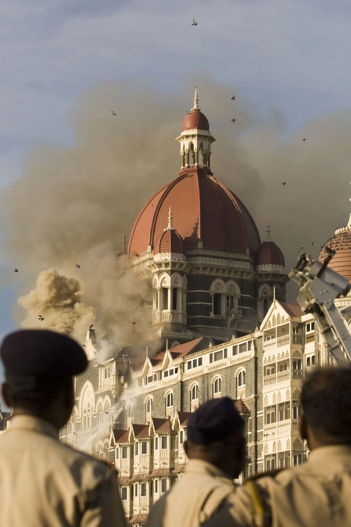 Security forces personnel watch as a fire rages in the Taj Mahal Palace and Tower hotel in Mumbai, India, in 2008 (Photographer: Prashanth Vishwanathan/Bloomberg)