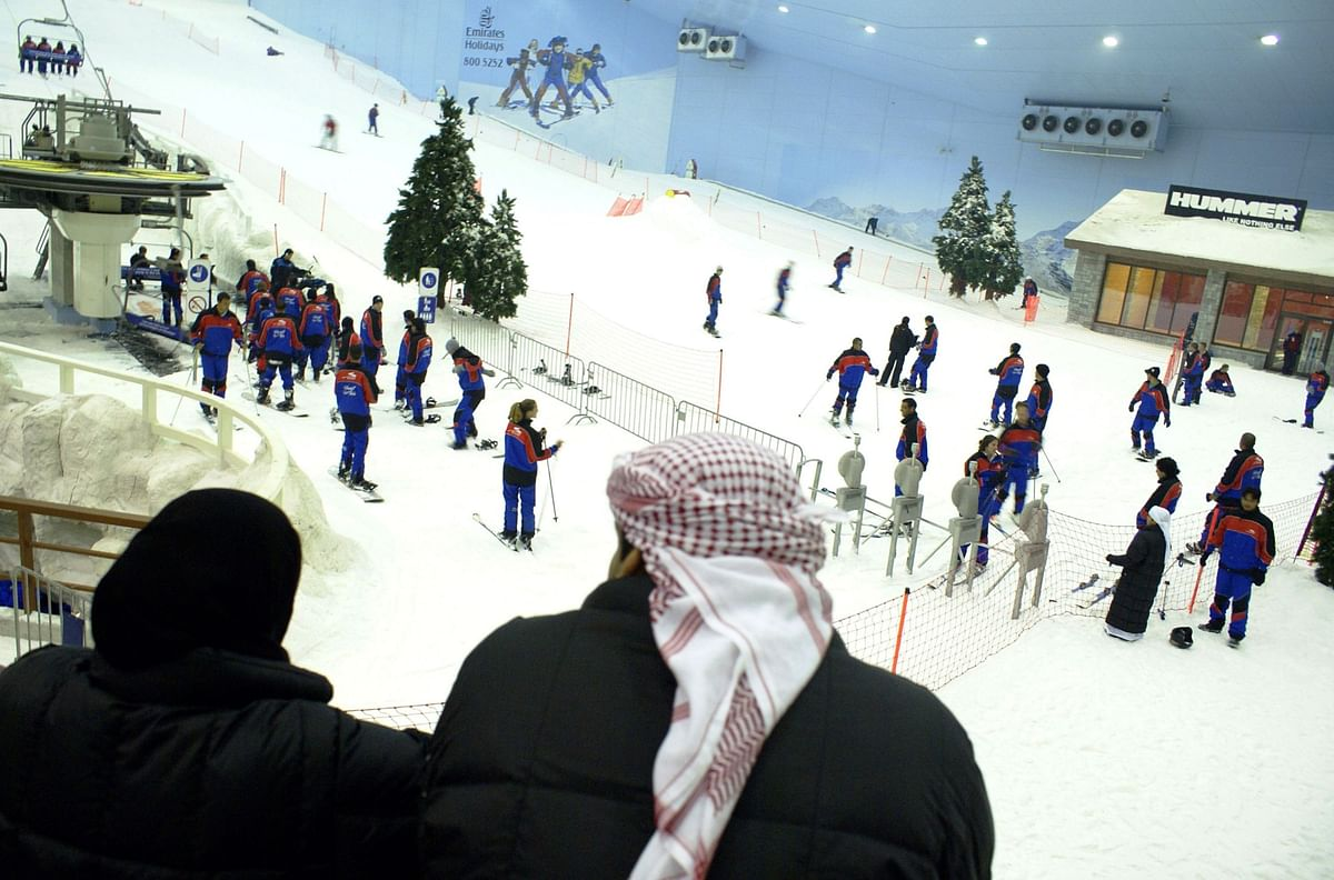 People watch skiers at Dubai Ski, in the Mall of the Emirates, in Dubai, UAE. (Photographer: Charles Crowell/Bloomberg News)