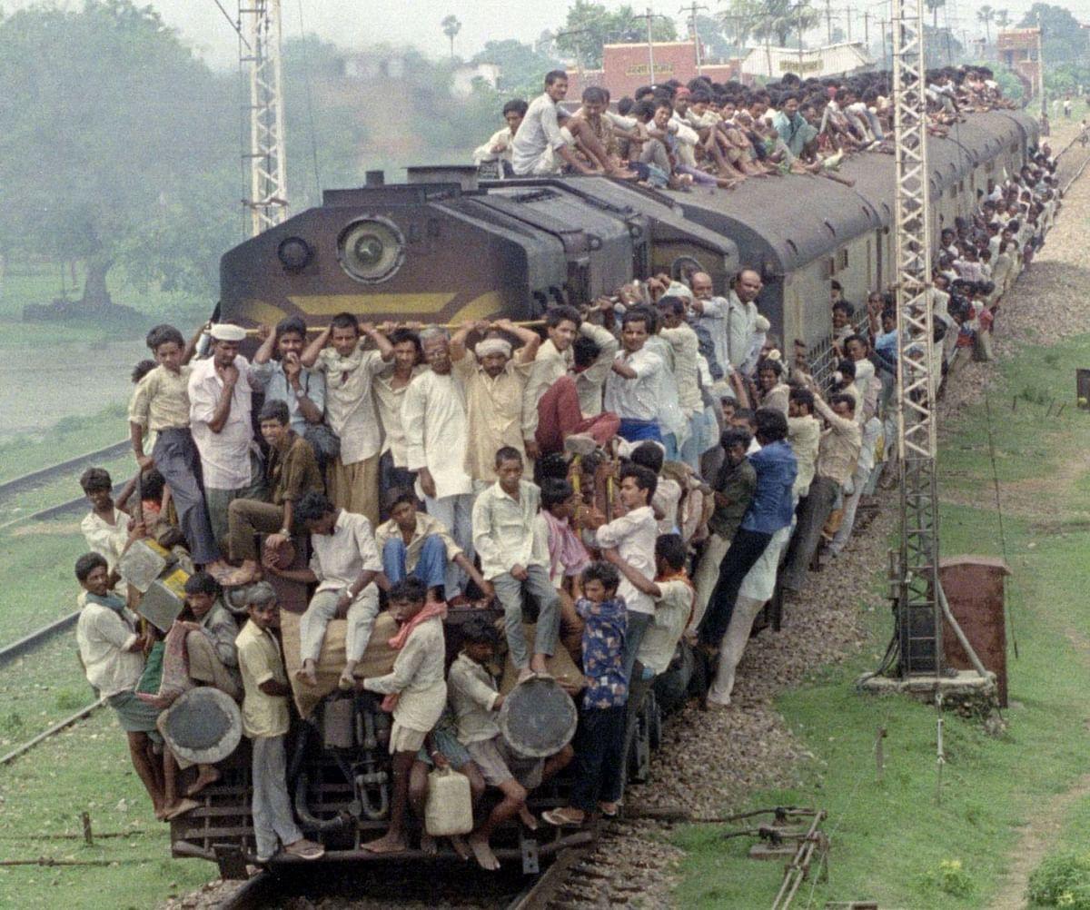 Passengers cover a crowded commuter train in Bihar, on Feb. 19, 2003. (Photographer: Sunil Malhotra/Bloomberg News)