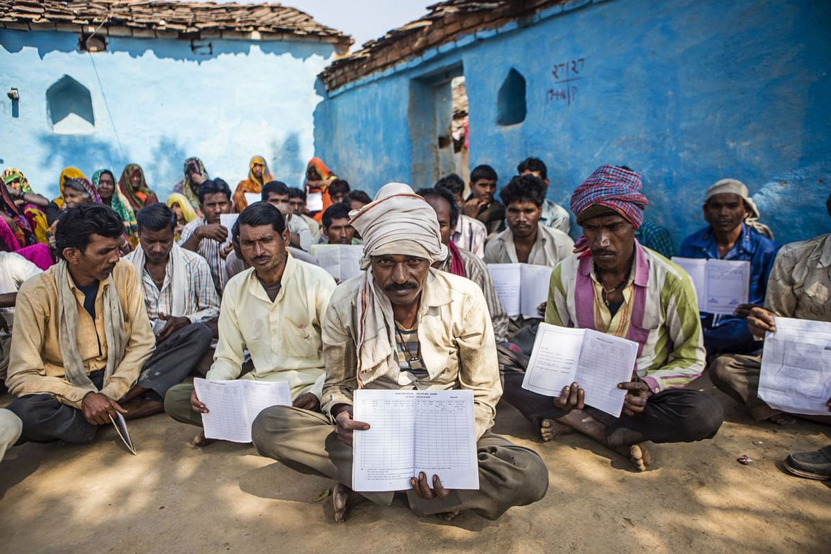 Gayadeen Adivasi and other villagers hold up their MGNREGA cards with no entries for the rural jobs program, during a public hearing in the village of Lar Sauryana in Tikamgarh, Madhya Pradesh, on Feb. 8, 2016. (Photographer: Prashanth Vishwanathan/Bloomberg)