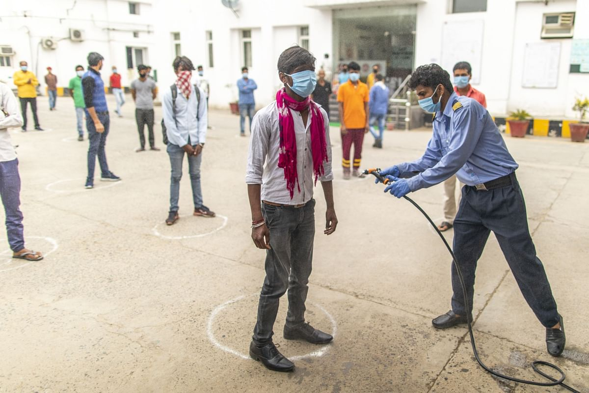 A security guard sprays a worker at a factory in Sonipat district, Haryana, on April 20, 2020. (Photographer: Prashanth Vishwanathan/Bloomberg)