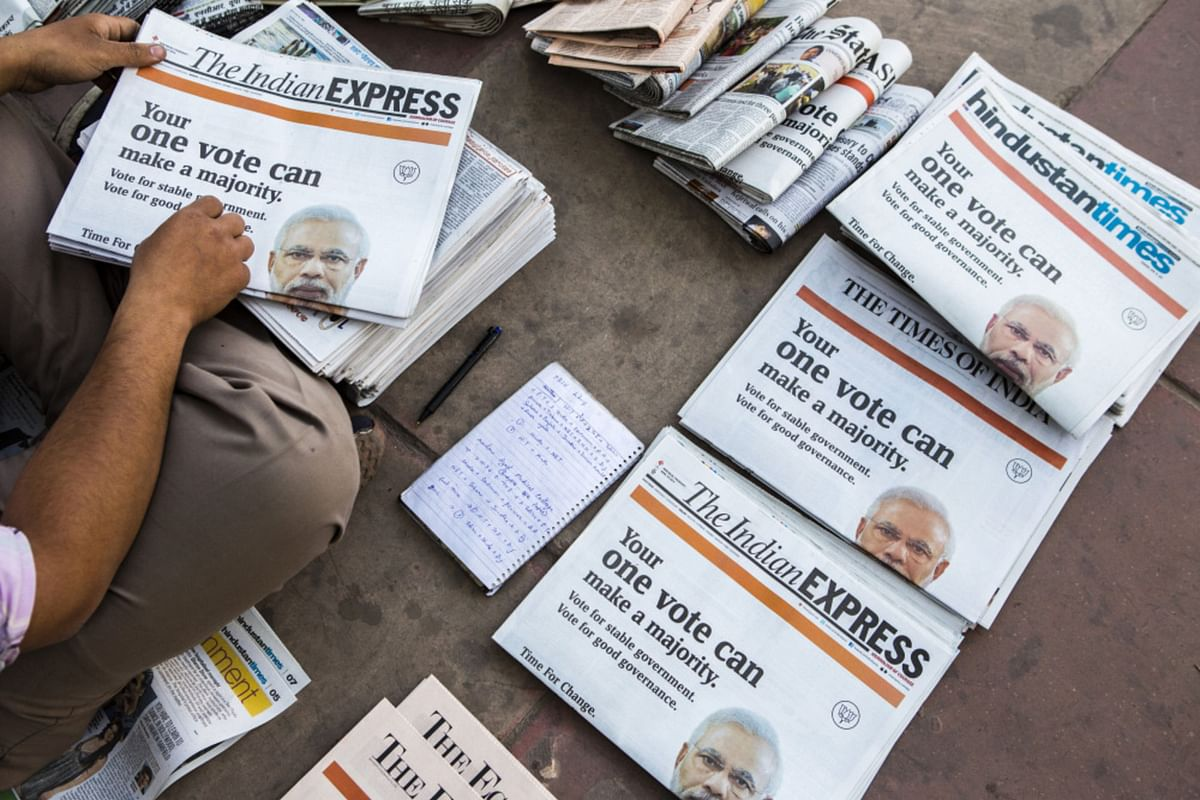 A vendor arranges copies of newspapers that feature a BJP wraparound cover advertisement ahead of voting for national elections in New Delhi, on April 10, 2014. (Photographer: Prashanth Vishwanathan/Bloomberg)