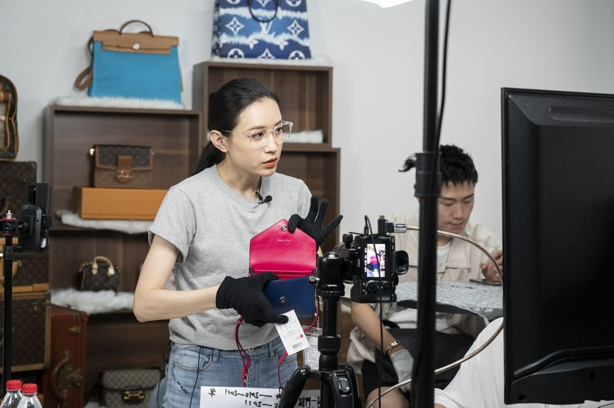 An influencer presents a handbag to the camera during a livestream event, in Beijing, on July 1, 2020. (Photographer: Giulia Marchi/Bloomberg)