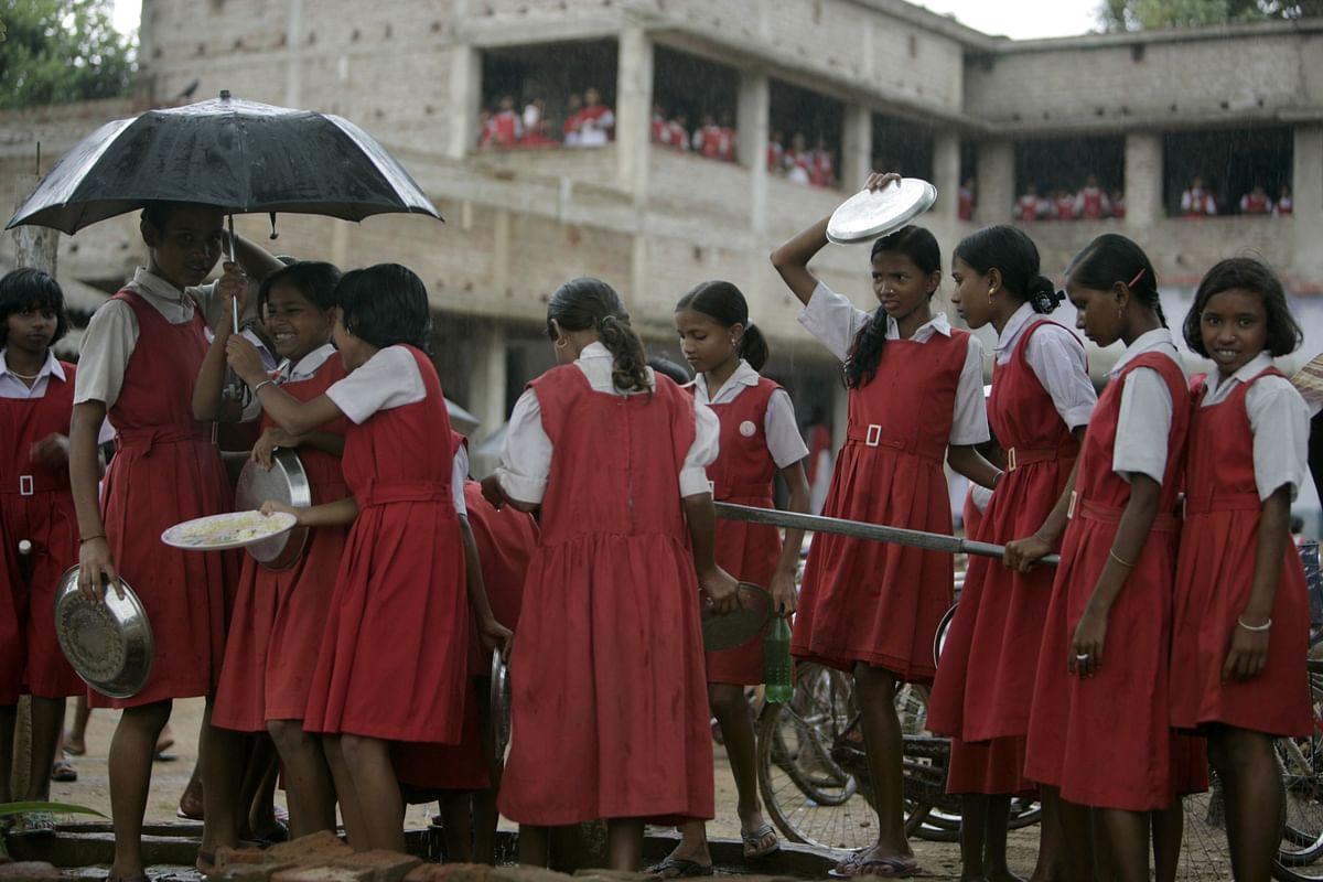 School girls gather around a hand pump to wash their food plates in Lalgarh, West Bengal. (Photographer: Adeel Halim/Bloomberg News)