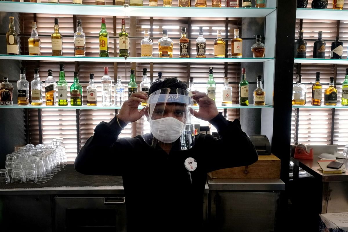A bartender wearing a protective mask adjusts his face shield at a restaurant, in New Delhi, on Sept. 8, 2020. (Photographer: T. Narayan/Bloomberg)