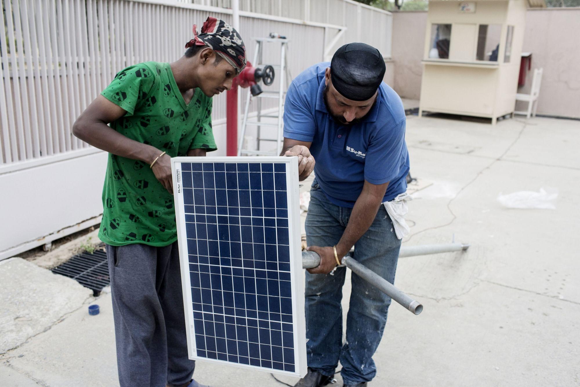 Workers install a solar panel in New Delhi. (Photographer: Udit Kulshrestha/Bloomberg)
