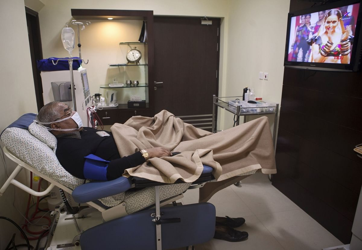 A patient watches a TV program as he undergoes dialysis, a Fortis Healthcare dialysis clinic in New Delhi. (Photographer: Prashanth Vishwanathan/Bloomberg)
