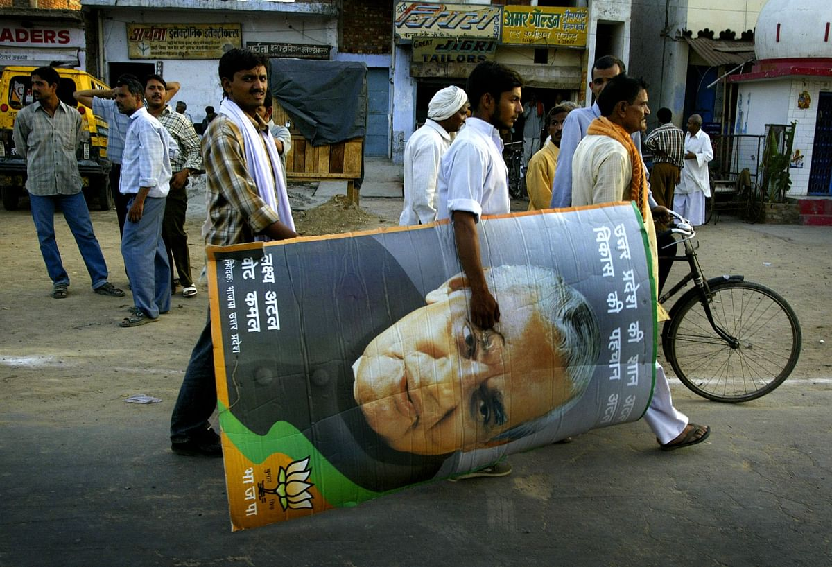 A BJP supporter carries a picture of Atal Bihari Vajpayee after an election rally in Aligarh, Uttar Pradesh, on April 29, 2004. (Photographer: Amit Bhargava/Bloomberg News)