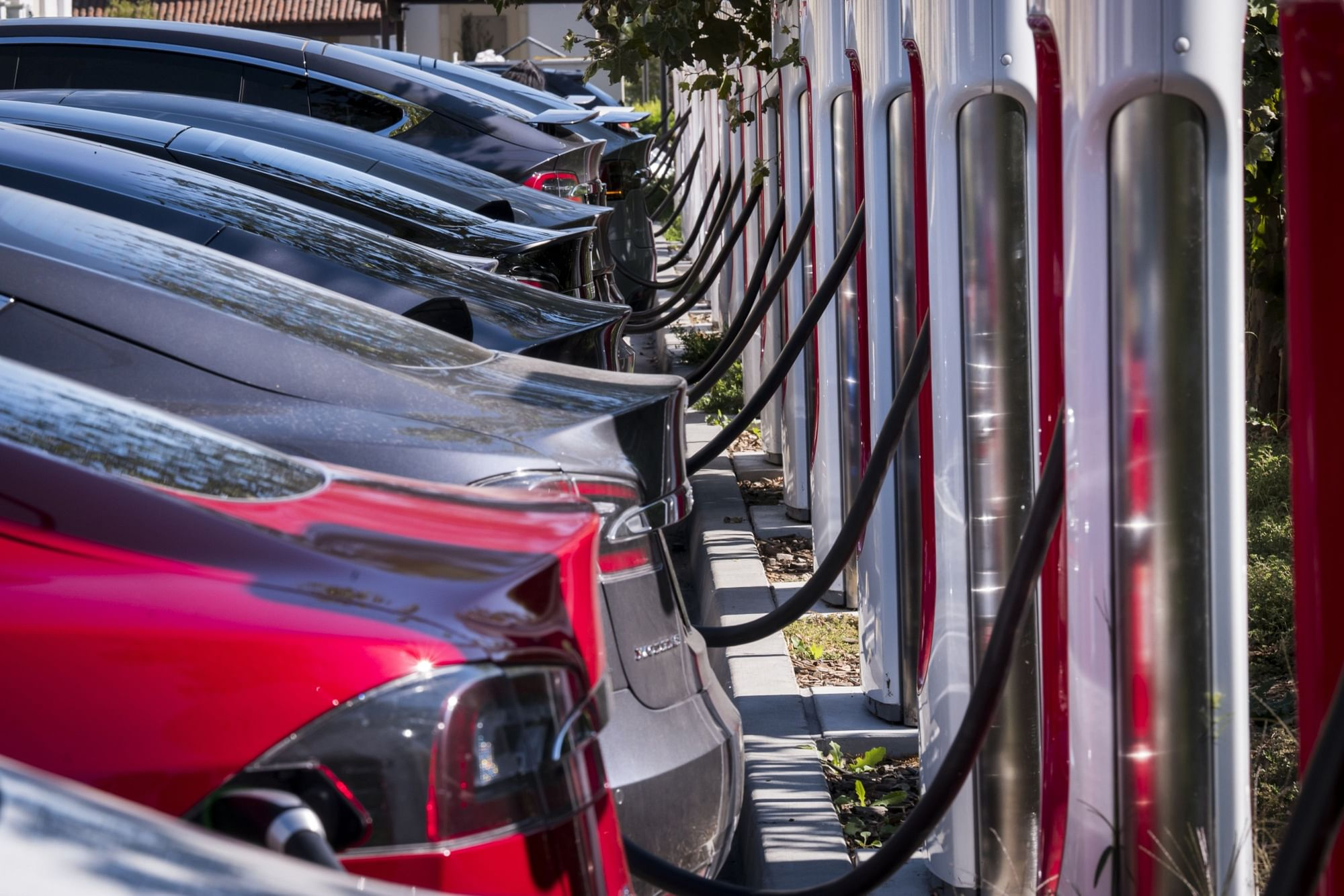 Tesla Inc. vehicles stand at a Tesla Supercharger station in Concord, California. (Photographer: David Paul Morris/Bloomberg)