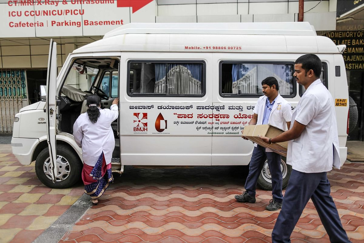 Medical staff carry equipment to a vehicle at a hospital in Bengaluru. (Photographer: Dhiraj Singh/Bloomberg)