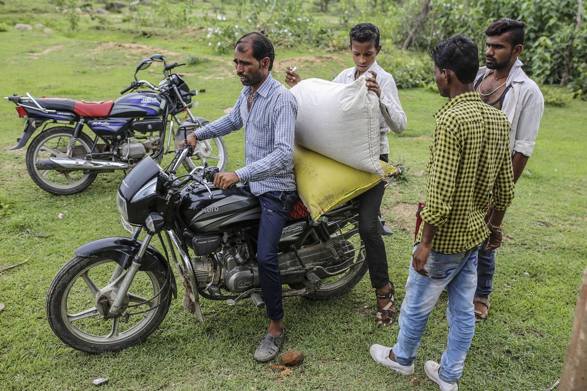 """<div class=""""paragraphs""""><p>People load a subsidized ration of grain onto a motorcycle outside a state-run distribution store in a village in Tikamgarh district, Madhya Pradesh, India. (Photographer: Dhiraj Singh/Bloomberg)</p></div>"""