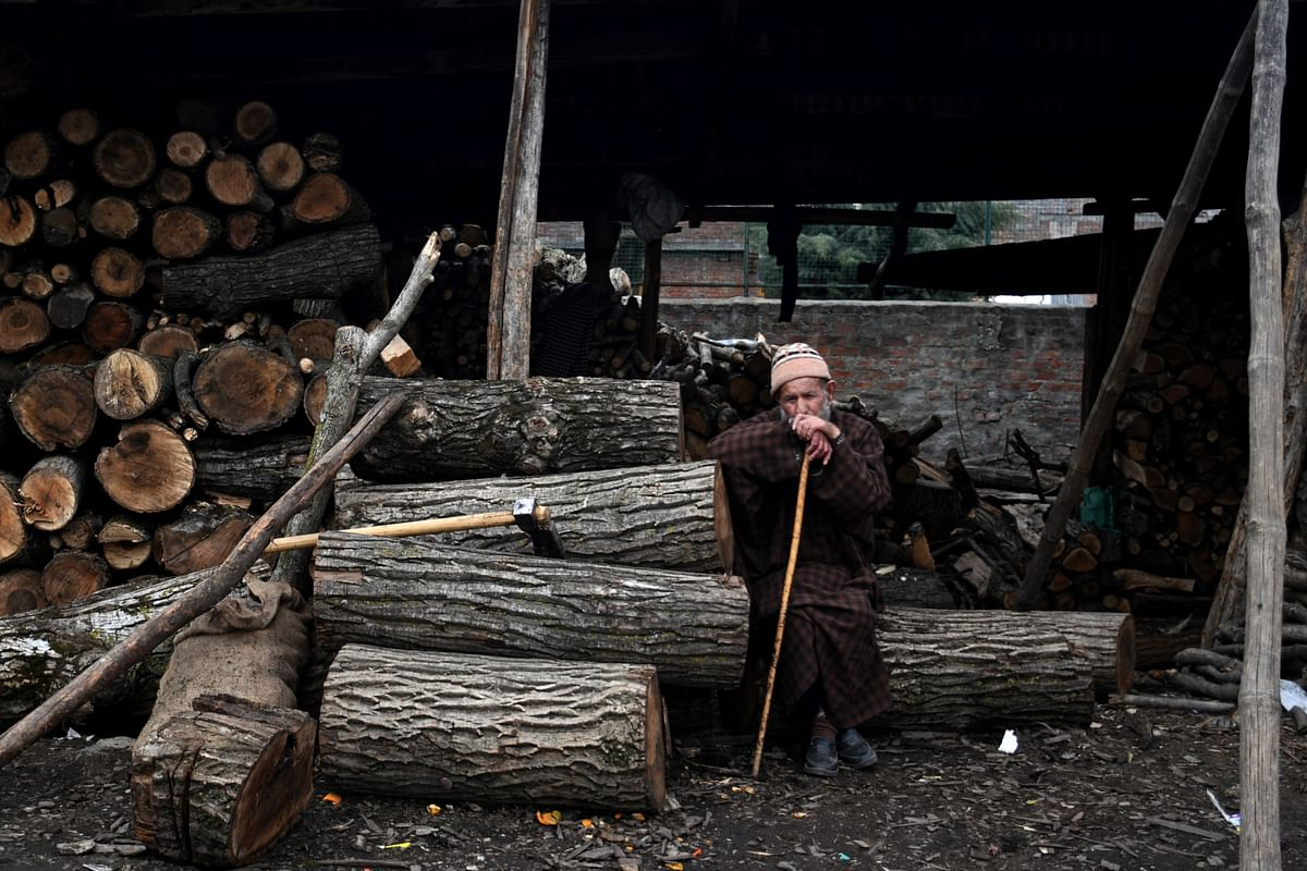 """<div class=""""paragraphs""""><p>A man with a cane sits next to timber at a store in Srinagar. (Photographer: Anindito Mukherjee/Bloomberg)</p></div>"""
