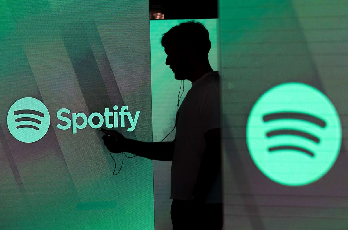 """<div class=""""paragraphs""""><p>A man checks his smartphone between screens bearing the Spotify logo,&nbsp;in London, on June 26, 2018. (Photographer: Chris Ratcliffe/Bloomberg)</p></div>"""