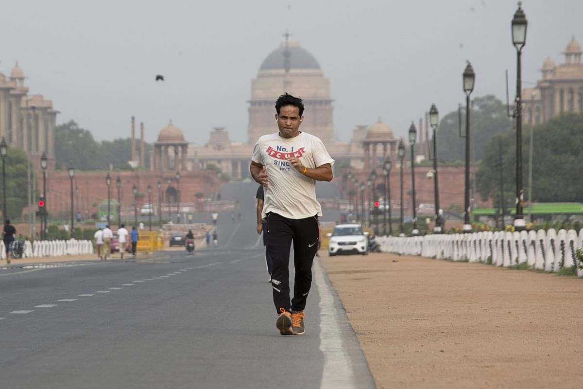 """<div class=""""paragraphs""""><p>A man jogs along Rajpath, as Rashtrapati Bhavan sits in the background in in New Delhi. (Photographer: Ruhani Kaur/Bloomberg)</p></div>"""