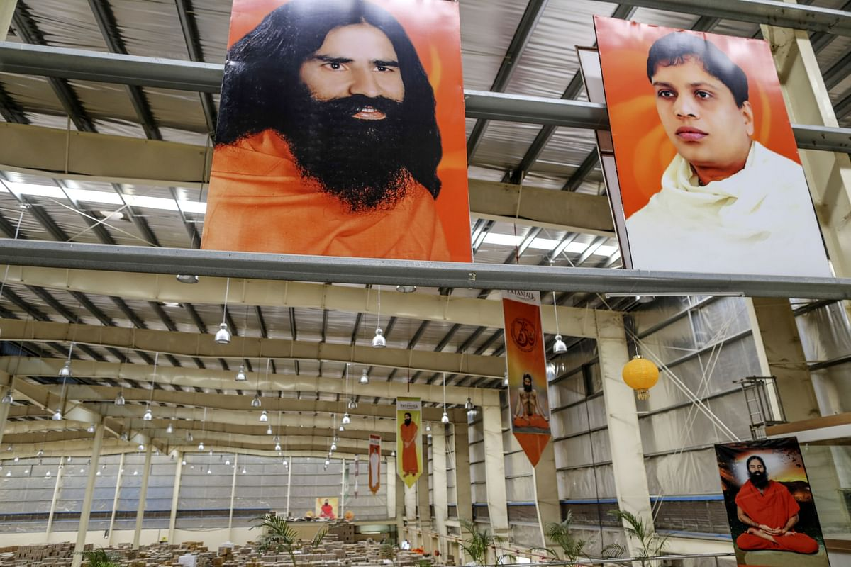 """<div class=""""paragraphs""""><p>Posters depicting yoga guru Baba Ramdev, top left, and Acharya Balkrishna, chief executive officer of Patanjali Ayurved Ltd., top right, are displayed inside a warehouse operated by the company in Nagpur, India. (Photographer: Dhiraj Singh/Bloomberg)</p></div>"""