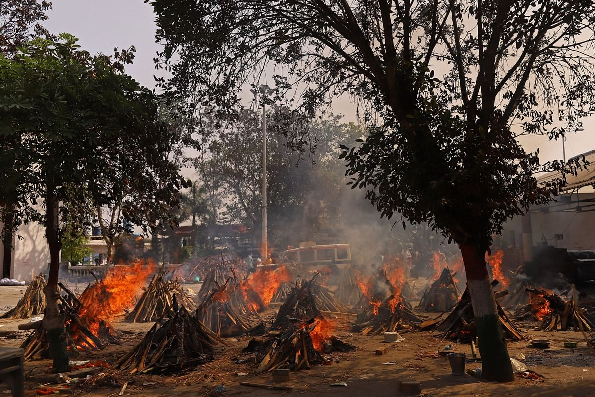 """<div class=""""paragraphs""""><p>Funeral pyres of Covid-19 fatalities burn at a crematorium in New Delhi. (Photographer: Anindito Mukherjee/Bloomberg)</p></div>"""