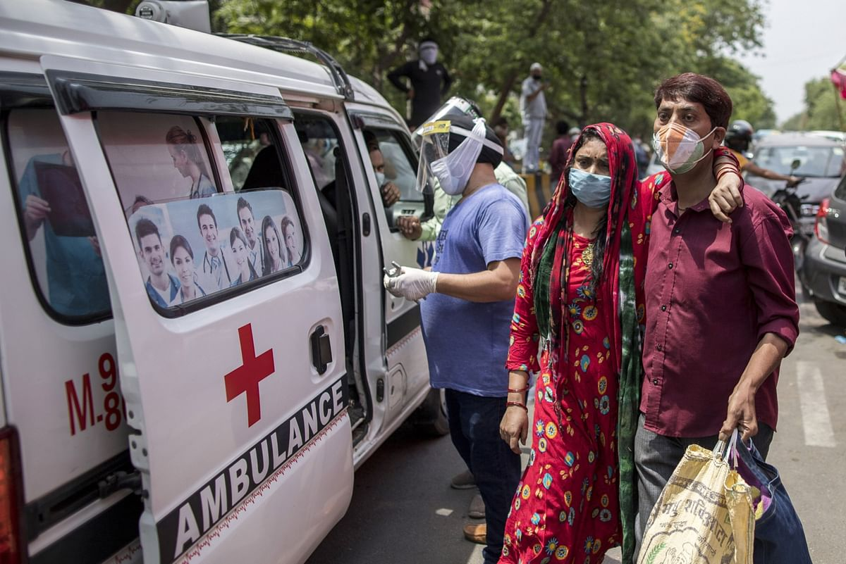 """<div class=""""paragraphs""""><p>A woman seeking medical oxygen is assisted as she arrives at a Gurdwara in New Delhi, India. (Photographer: Anindito Mukherjee/Bloomberg)</p></div>"""