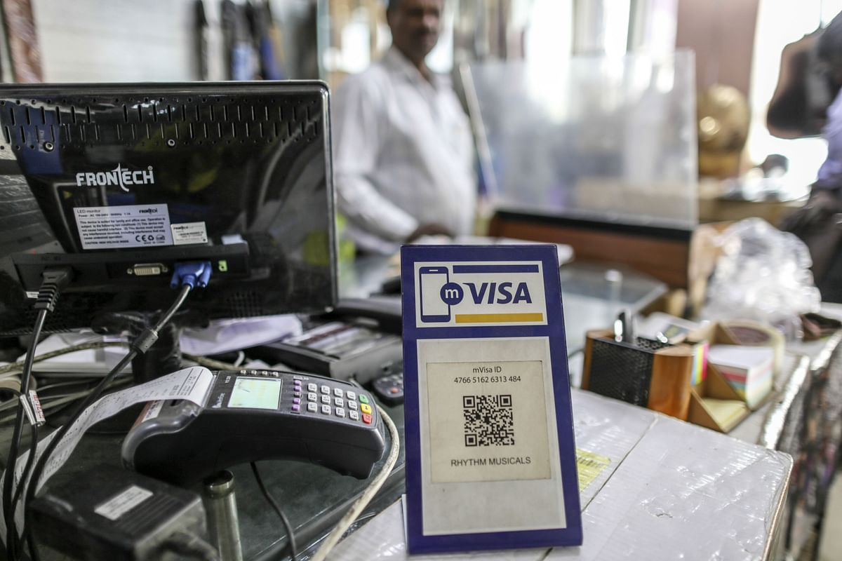 """<div class=""""paragraphs""""><p>Signage for digital payment service mVisa, operated by Visa Inc., is displayed at a store selling musical instruments in Bengaluru. ( Photographer: Dhiraj Singh/Bloomberg)</p></div>"""