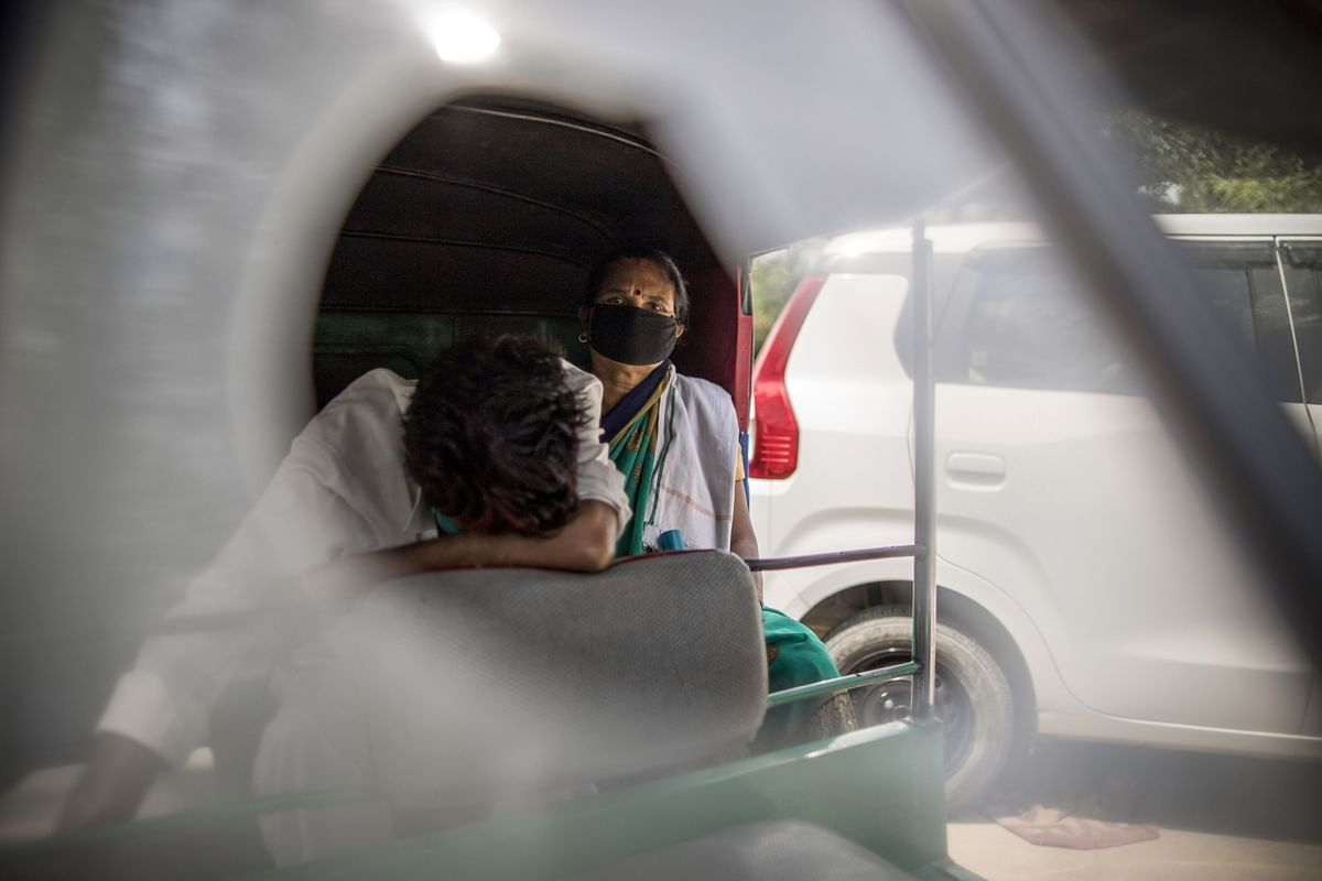 """<div class=""""paragraphs""""><p>A woman waits with her son in a rickshaw they seek medical oxygen at a Gurdwara in New Delhi, India. (Photographer: Anindito Mukherjee/Bloomberg)</p></div>"""