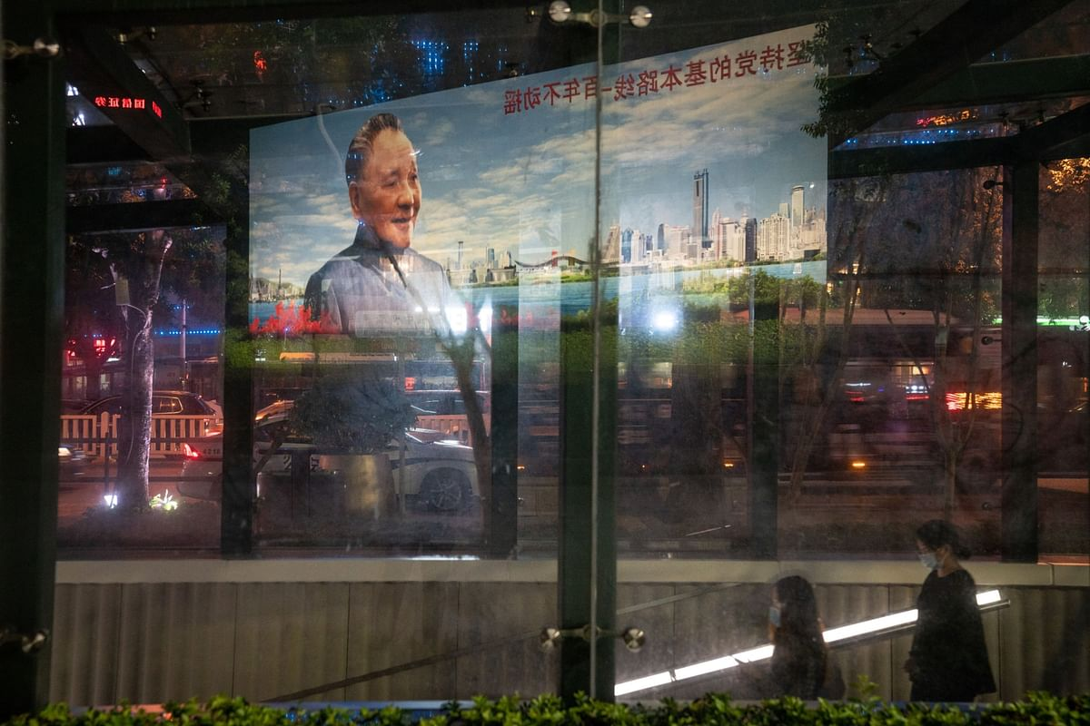 """<div class=""""paragraphs""""><p>A portrait of Deng Xiaoping is reflected on the glass wall of an underpass entrance near Deng Xiaoping Portrait Square in Shenzhen, China. (Photographer: Yan Cong/Bloomberg)</p></div>"""