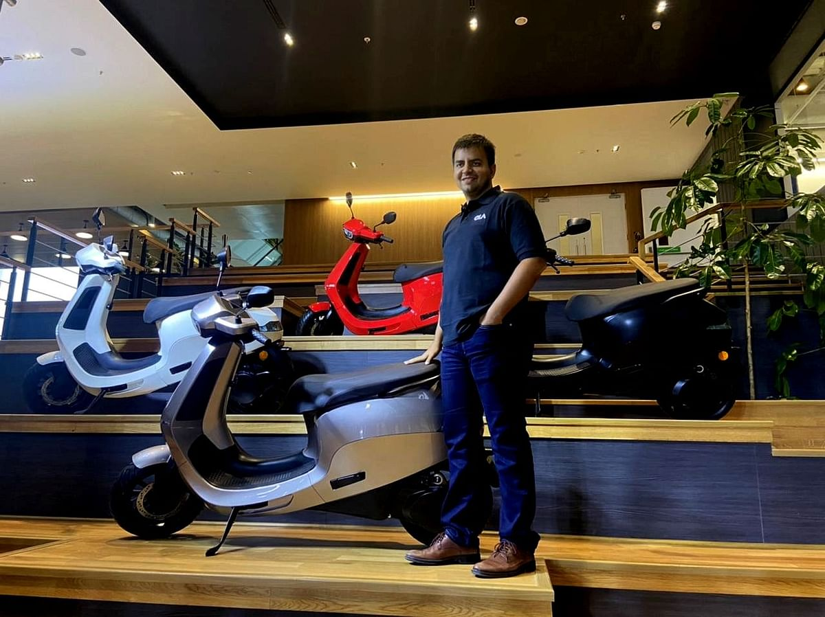 """<div class=""""paragraphs""""><p>Bhavish Aggarwal, CEO of Ola Group, poses with the company's electric scooter for a photograph. (Photo: BloombergQuint)</p></div>"""