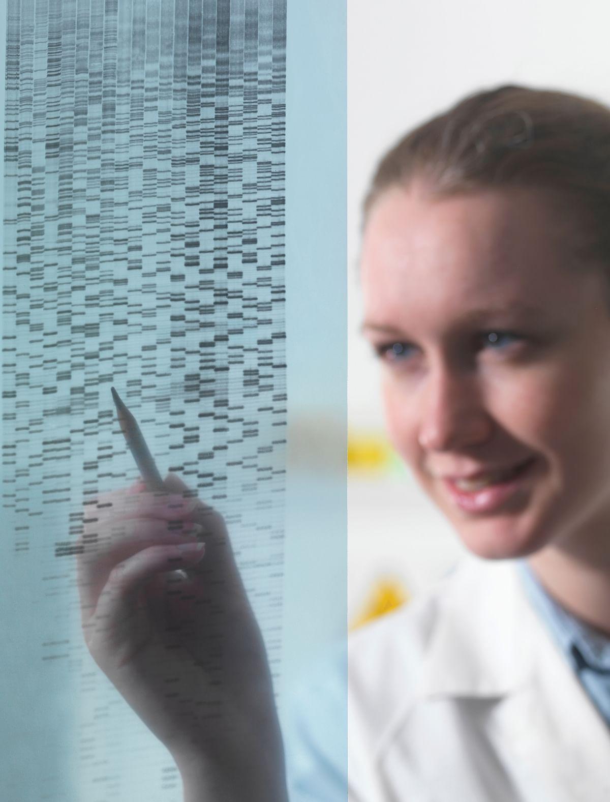 Female researcher examining DNA autoradiogram gel in laboratory