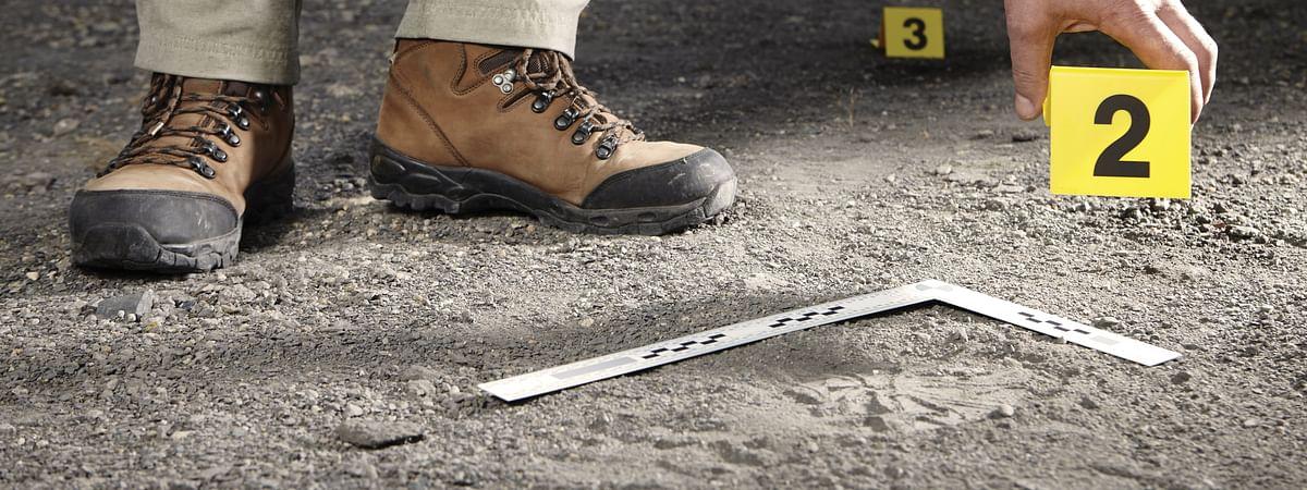 A crime scene investigator documents footwear evidence.