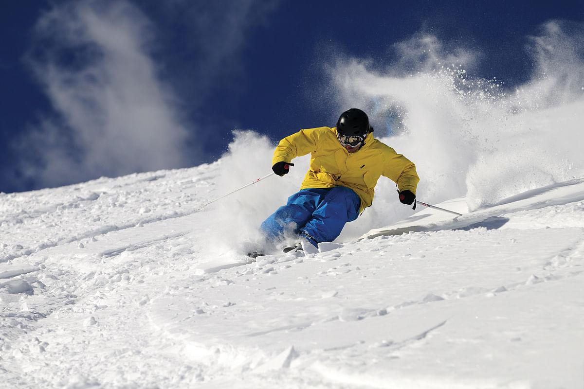 Freeride skier in powder snow against blue sky