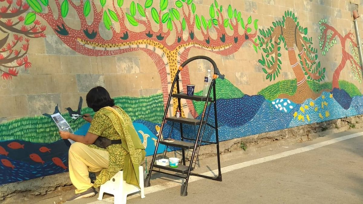 Abha lending finishing touches to the wall painting mural by the people
